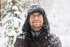 Man in fur winter hat with ear flaps smiling portrait. Extreme in the forest Stock Photography