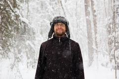 Man in fur winter hat with ear flaps smiling portrait. Extreme in the forest Royalty Free Stock Photography