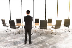 Man and furniture in a conference room with concrete floor Royalty Free Stock Photos
