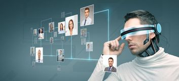 Man with futuristic 3d glasses and sensors. People, technology, future and progress - men with futuristic 3d glasses and microchip implant or sensors over blue Royalty Free Stock Images
