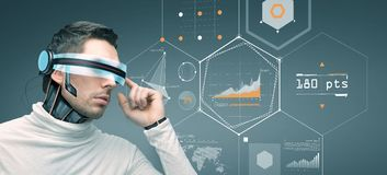 Man with futuristic 3d glasses and sensors. People, technology, future and progress - man with futuristic 3d glasses and microchip implant or sensors over gray Stock Images