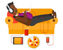Man with gadgets lying on sofa. A fat african-american man in headphones lying on a sofa with electronic devices and fast food vector flat design illustration vector illustration
