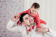Man gaily spends time with the little daughter. Charming baby sits on shoulders at the father and cheerfully laughs. Stock Images