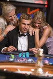 Man gambling in casino. Man gambling surrounded by attractive women at roulette table Stock Photo