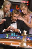 Man gambling at casino. Surrounded by glamorous women at roulette table Royalty Free Stock Photo