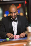 Man gambling in casino at roulette table. Man sitting at roulette table in casino Stock Images