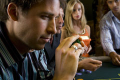 Man with gambling chips at table, side view Stock Image