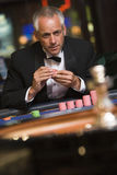 Man gambling at roulette table Stock Images