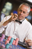 Man gambling at roulette table Stock Image