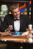 Man gambling at roulette table in casino Stock Photo