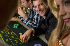 Man gambling at roulette table, smiling, portrait stock photos