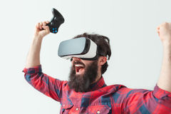Man with gamepads in VR headset Stock Photo