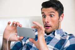 Man gaming on smartphone. Portrait of a funny man gaming on smartphone at home stock photo