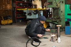 Man in the garage, with flame burning gas welding. Work man is a welder in mask, metal product at home garage, with flame burning gas welding Royalty Free Stock Photo