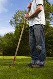 Man in garden. Man standing with garden tool on grass lawn Royalty Free Stock Images