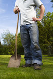 Man in garden. Man standing with shovel on grass lawn Stock Photo