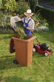 Man in the garden, compost bin. Man with blue overalls and a plaid shirt and straw hat standing in the garden next to the lawn mower and the compost bin filled Stock Photos