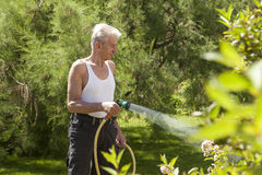 Man with garden hose Royalty Free Stock Photography