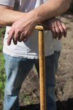 Man with a garden spade. A man relying on a garden spade in the sun, with arms crossed Royalty Free Stock Image
