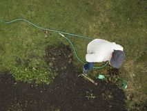 Man and  garden water hose. A man standing next to a garden water hose dropped on the ground, overhead view stock photo