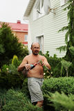 Man gardener with clippers in hand making art cutting juniper. Royalty Free Stock Photos