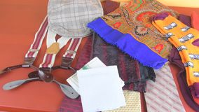 Man garments. Clothing concept for men. Colorful socks, ties, braces, scarfs and checked flat cap on claret background