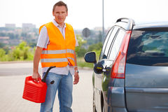 Man with gas can. Man with gas tank standing near his car royalty free stock photography