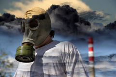 Man in a gas mask. Against a pipe polluting air Royalty Free Stock Images