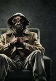 Man in gas mask. Sitting in a chair Stock Image