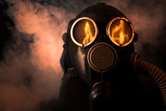 Man in gas mask. With fire reflection in the eyes Royalty Free Stock Photography