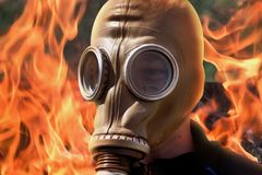 Man in gas mask on background of fire during fire. Taming fir stock image