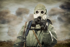 Man in gas mask with binocular. On war stock photo