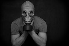 The man in a gas mask on a black background. Stock Photos