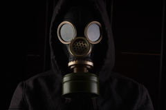 Man with gas mask. Man with gas mask on black background and dim light Stock Photo