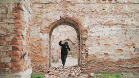 Man in gas mask and black clothes runs on an abandoned ruined building. Stalker concept, survivor after nuclear chemical war.