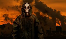 Man in gas mask and cloak of chemical protection with heavy industry plants. Man in gas mask and cloak of chemical protection with heavy industry plant on royalty free stock photo