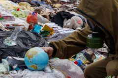 A man in a gas mask found a globe in the dump. People destroy the planet earth. The world is mired in plastic debris. The concept. A man in a gas mask found a stock image