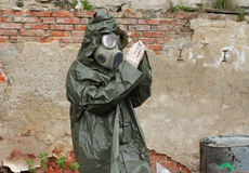 Man with gas mask and green military clothes  explores  small pl Stock Images