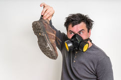Man with gas mask is holding dirty stinky shoe. Unpleasant smell concept stock photography