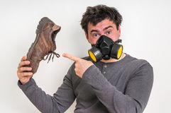 Man with gas mask is holding dirty stinky shoe. Unpleasant smell concept stock photos