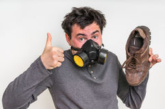 Man with gas mask is holding dirty stinky shoe. Unpleasant smell concept stock images