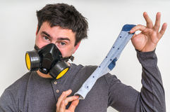 Man with gas mask is holding dirty stinky sock. Unpleasant smell concept royalty free stock photos