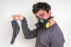 Man with gas mask is holding dirty stinky sock. Unpleasant smell concept stock photos