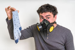 Man with gas mask is holding dirty stinky sock. Unpleasant smell concept royalty free stock photo