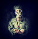 Man in gas mask holding flower in palms Royalty Free Stock Photos