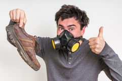 Man with gas mask is holding stinky shoe. Unpleasant smell concept stock image
