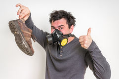 Man with gas mask is holding stinky shoe. Unpleasant smell concept royalty free stock photo
