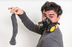 Man with gas mask is holding stinky sock. Unpleasant smell concept stock images