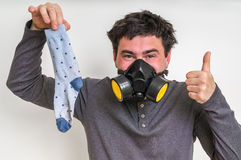 Man with gas mask is holding stinky sock. Unpleasant smell concept royalty free stock images