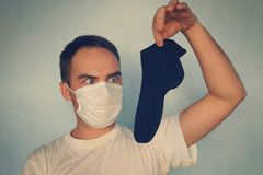 Man with gas mask is holding stinky sock - unpleasant smell concept. Man with gas mask is holding stinky sock - unpleasant smell concept, medical face mask royalty free stock photos